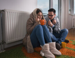 Couple sitting beside radiator and freezing
